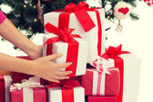 Close up of woman with presents and christmas tree — Stock Photo