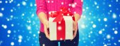 Close up of woman in pink sweater holding gift box — Stock Photo