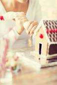 Close up of woman making gingerbread house at home — Stockfoto