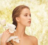Mulher jovem e bonita com flores da orquídea — Foto Stock