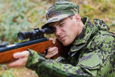 Young soldier or hunter with gun in forest — Stock Photo