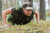 Young soldier or ranger doing push-ups in forest — Stock Photo
