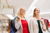 Happy young women with shopping bags in mall — Стоковое фото