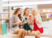 Happy women with smartphones and shopping bags — Stock Photo