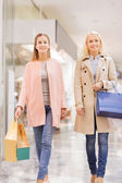Happy young women with shopping bags in mall — Stok fotoğraf
