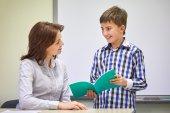 School boy with notebook and teacher in classroom — Zdjęcie stockowe