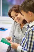 School boy with notebook and teacher in classroom — Stok fotoğraf