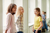 Group of smiling school kids in corridor — Stok fotoğraf