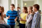 Group of school kids with soda cans in corridor — Stock Photo