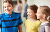 Group of smiling school kids talking in corridor — Stock Photo