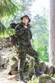 Young soldier with backpack in forest — Stock Photo