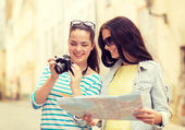 Lachende tienermeisjes met kaart en camera — Stockfoto