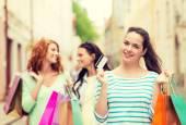 Lachende tienermeisjes met boodschappentassen op straat — Stockfoto