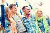 группа улыбающихся друзей в парке развлечений — Стоковое фото