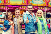 Group of smiling friends showing thumbs up — Stockfoto