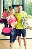 Usmívající se pár s lahví s vodou v tělocvičně — Stock fotografie