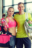 Smiling couple with water bottles in gym — Foto de Stock