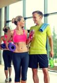 Smiling couple with water bottles in gym — Stock fotografie