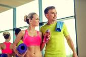 Smiling couple with water bottles in gym — Foto Stock