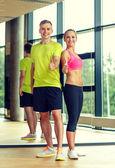 Homem e mulher aparecendo polegares no ginásio a sorrir — Foto Stock