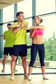 Usmívající se muž a žena, cvičení v tělocvičně — Stock fotografie