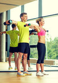 Smiling man and woman with dumbbells in gym — Foto de Stock