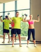Homem e mulher com halteres no ginásio a sorrir — Foto Stock