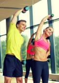 улыбающийся мужчина и женщина с гантелями в тренажерном зале — Стоковое фото