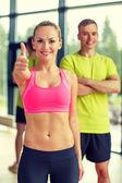 улыбающийся мужчина и женщина показывает палец вверх в тренажерном зале — Стоковое фото