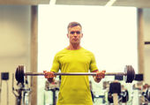 Man doing exercise with barbell in gym — Stock fotografie