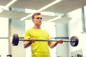 Man doing exercise with barbell in gym — Foto de Stock