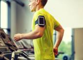 Man with smartphone exercising on treadmill in gym — Stock Photo