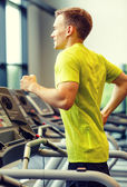 Smiling man exercising on treadmill in gym — Stock Photo
