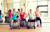 Grupo de mujeres sonrientes mostrando los pulgares para arriba en gimnasio — Foto de Stock