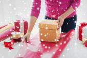 Close up of woman decorating christmas presents — Stock Photo