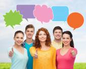 Group of smiling teenagers with text bubbles — Stock Photo