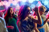 Smiling friends dancing in club — Stock Photo