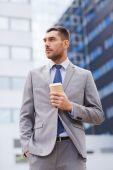 Jonge ernstige zakenman met papier kop buitenshuis — Stockfoto