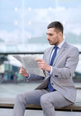 Young serious businessman newspaper outdoors — Stock Photo
