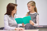 School girl with notebook and teacher in classroom — Стоковое фото