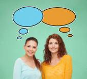 улыбающиеся студенческие девочки с текстовыми пузырями — Стоковое фото