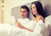 улыбаясь пара в постели с компьютеров tablet pc — Стоковое фото