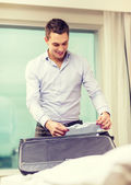 Businessman packing things in suitcase — Stock fotografie