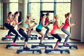 Group of women with dumbbells and steppers — Foto Stock