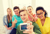 Five smiling students taking picture with camera — Stock Photo