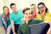 Lachende studenten maken selfie met tablet pc — Stockfoto