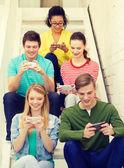 Estudiantes sonrientes con smartphone mensajes de texto en la escuela — Foto de Stock