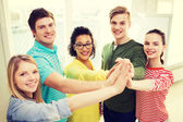 Five smiling students giving high five at school — Stock Photo