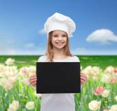 Little cook or baker with blank black paper — Stock fotografie
