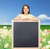 Happy little girl with blank blackboard — Stock fotografie
